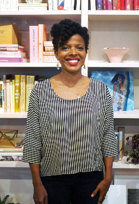 A black woman wearing red lipstick and smiling in front of a bookshelf