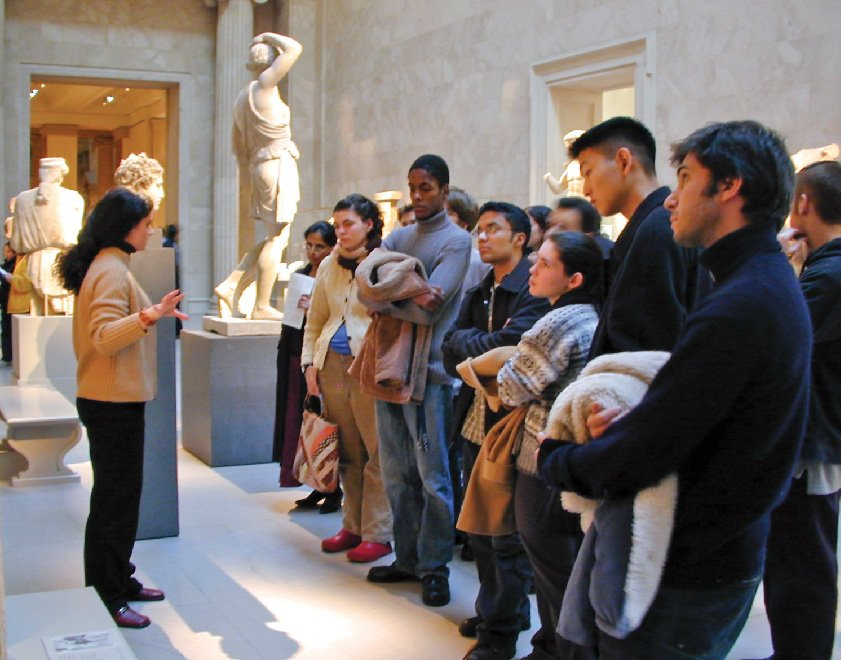 A group of students listening a docent in a sculpture gallery