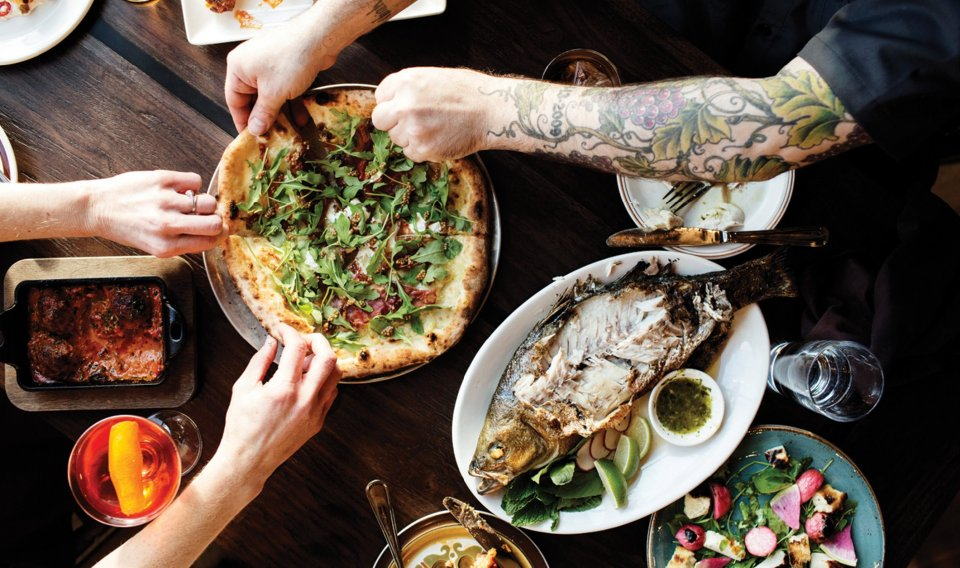 The hands and arms of several people reaching for portions of a pizza pie on a wooden table.