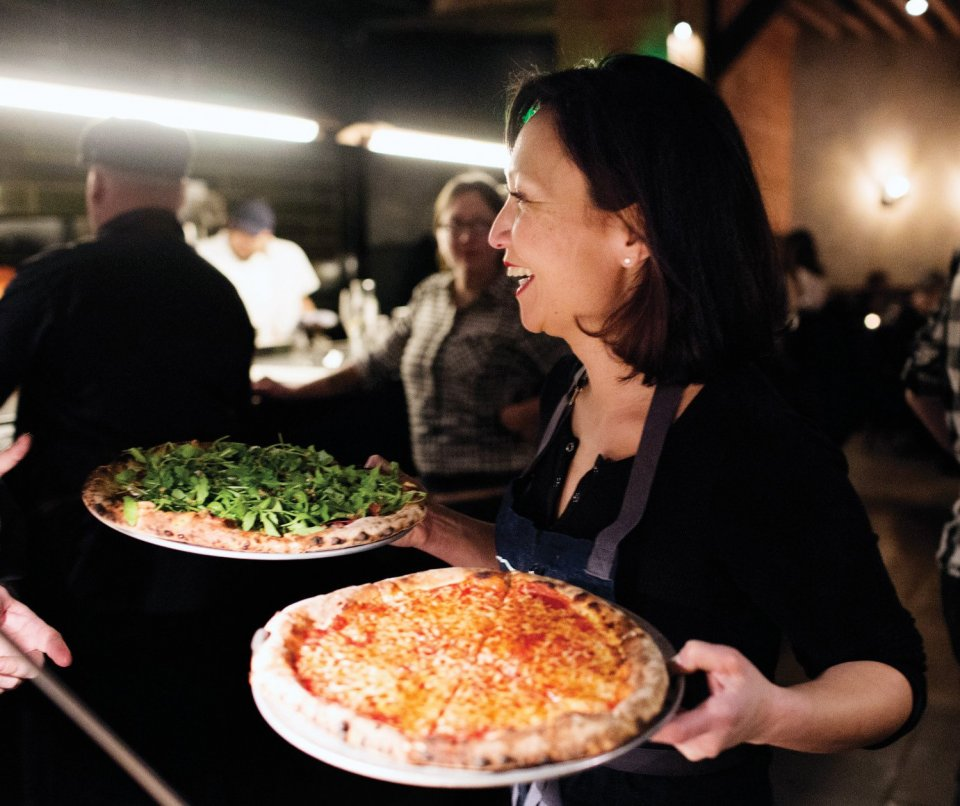 A woman smiling holding two pizzas in dishes