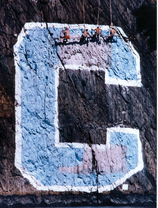 "Four rowers apply paint to a large ""C"" insignia located on a cliff."