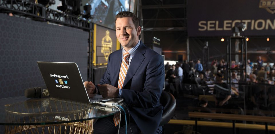 A white man in a suit sitting at a laptop, smiling