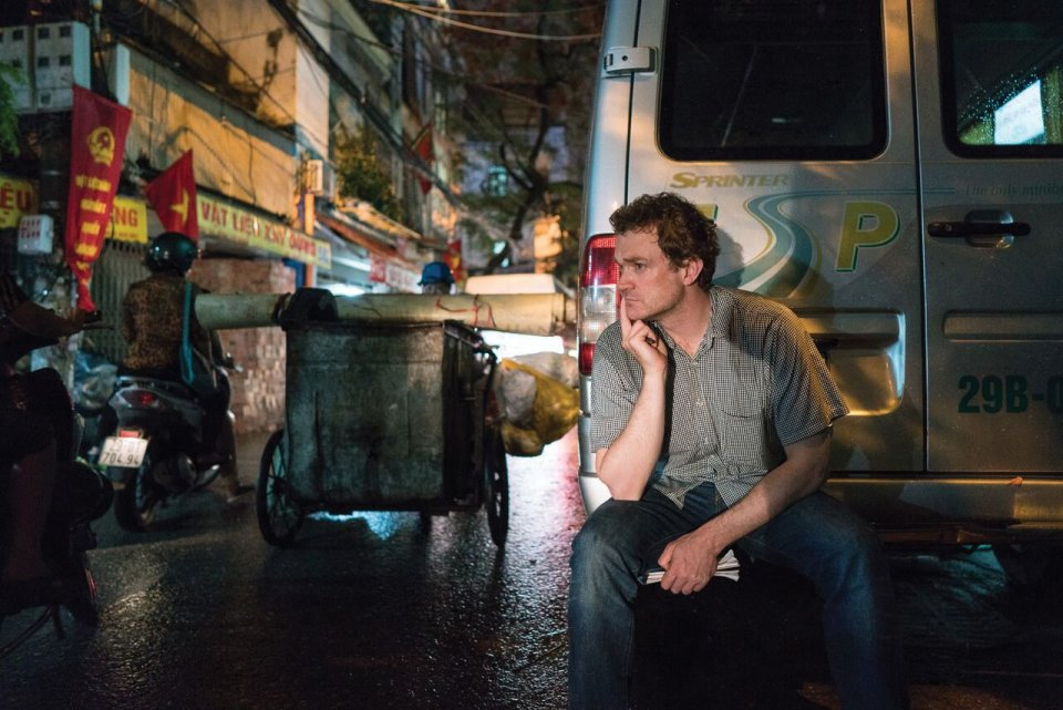 A man crouching behind a van.