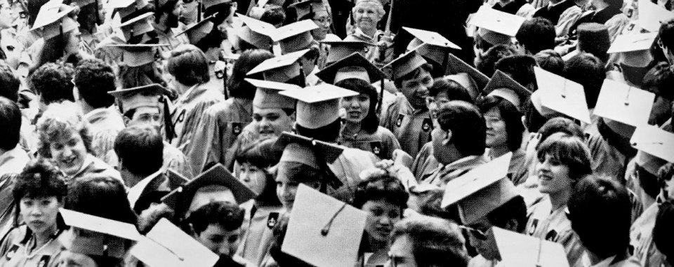 Black and white photo of young people wearing mortarboards