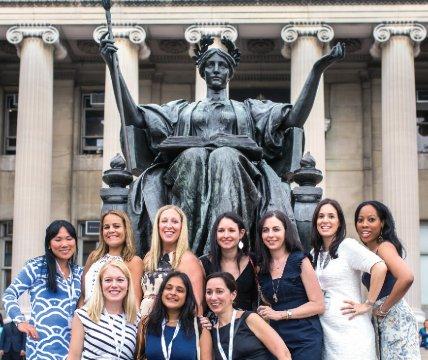 Alumni posing in front of Alma Mater