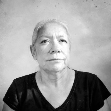 A white-haired woman in a black t-shirt