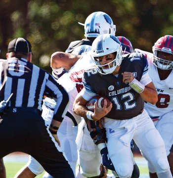 A Columbia Lions football player with jersey # 12 running with the ball.