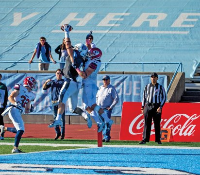 Columbia Lions football player in the air holding a football, with an opposing player behind him, also in the air, reaching for the ball.