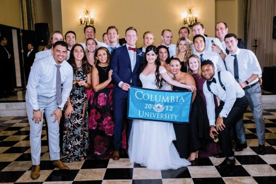 wedding party with Columbia banner