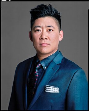 An Asian man in a blue suit with a pocket square