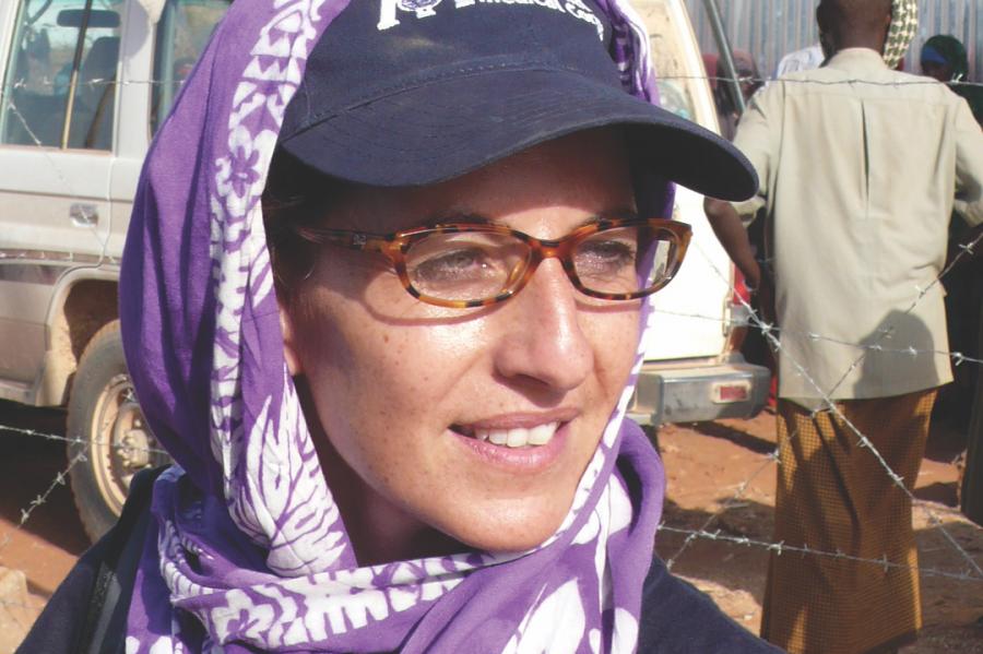 A white woman in a purple baseball cap